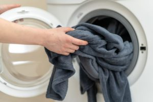 blanket being placed into washing machine