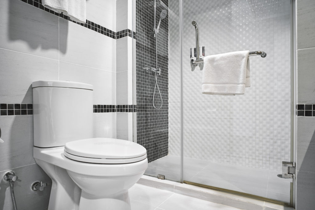 Toilet in a modern bathroom with white walls and gray accents