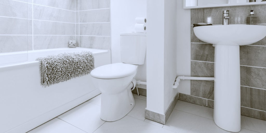 Small toilet in white bathroom with gray wall tiles