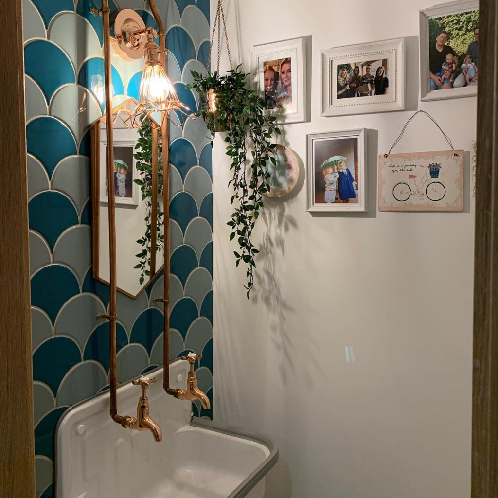 bathroom with mermaid backsplash and copper faucets Bathroom Lighting Ideas