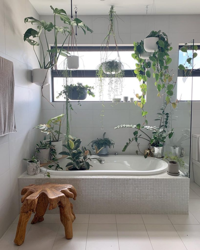 bathroom with many plants incorporated into it and natural wood stool Bathroom Lighting Ideas