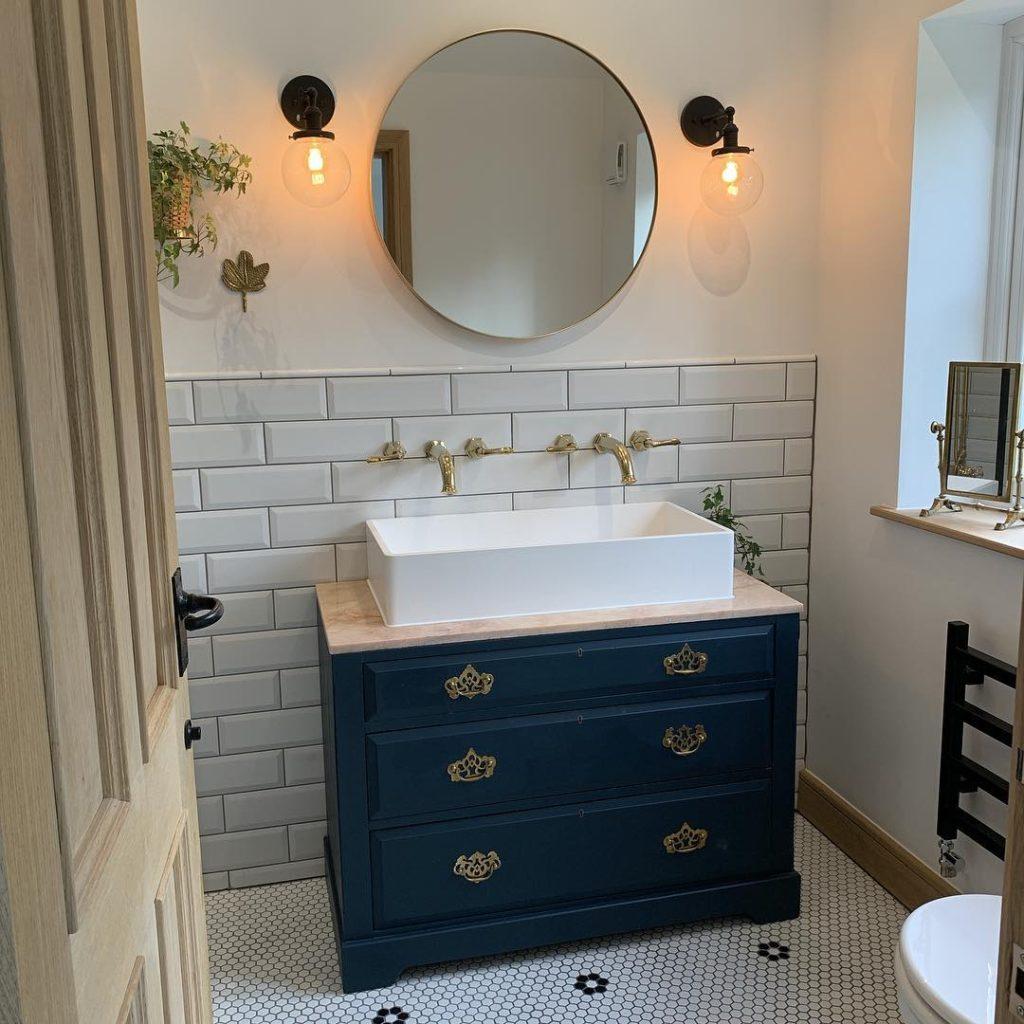 bathroom with navy blue vanity and circle mirror Bathroom Lighting Ideas