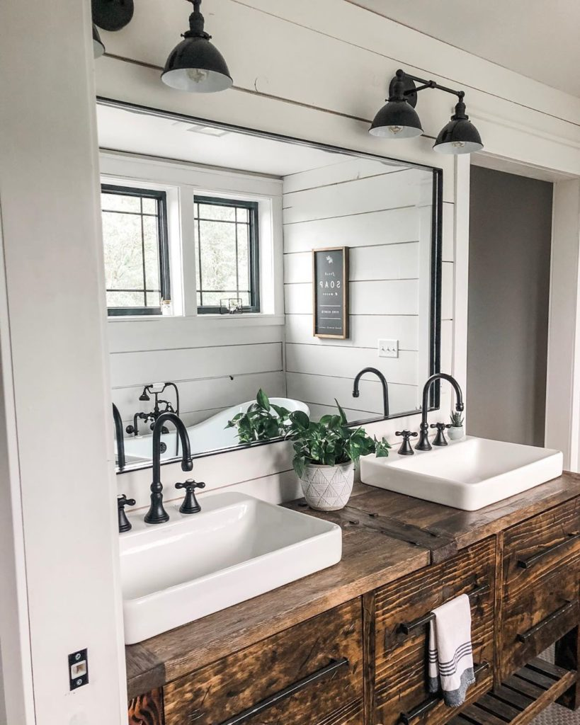 shiplap walls with rustic vanity in bathroom and black accents faucet Bathroom Lighting Ideas