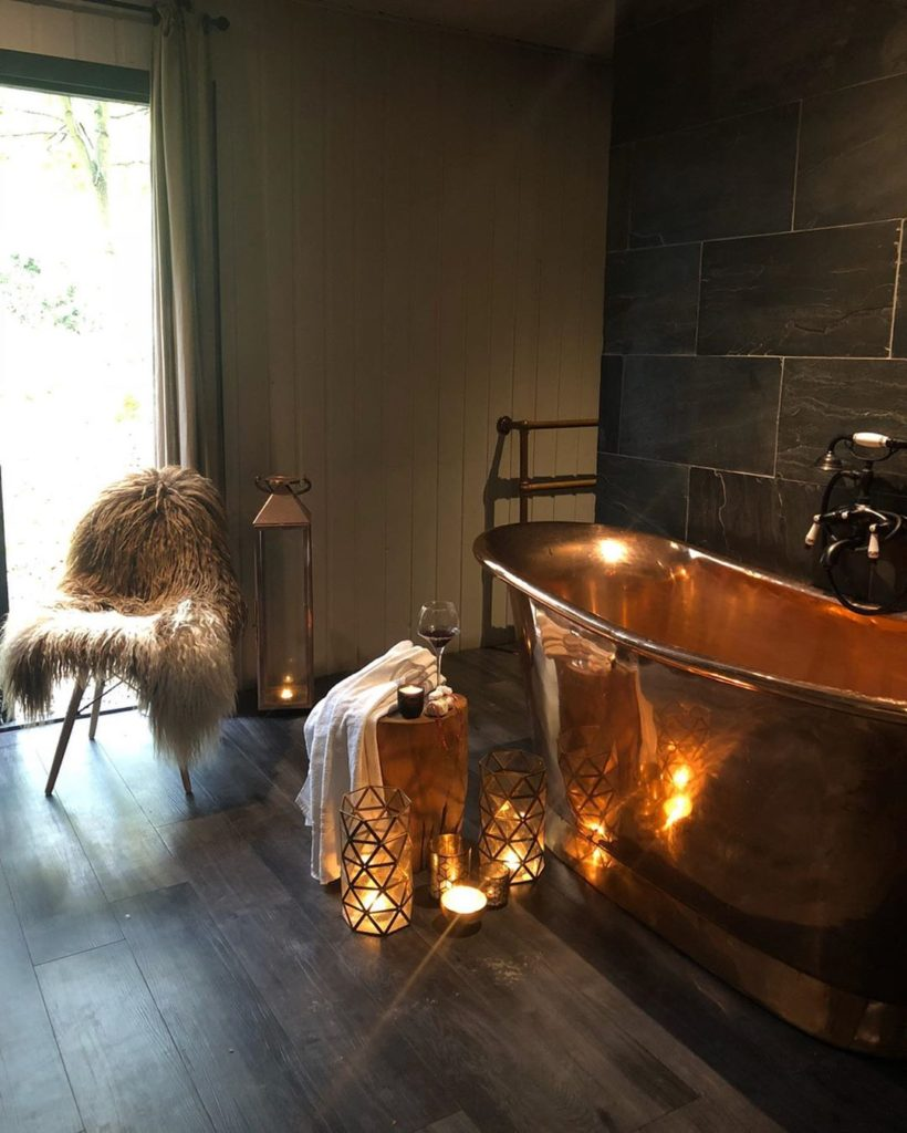 copper bathtub with fur accent and relaxing candles Bathroom Lighting Ideas