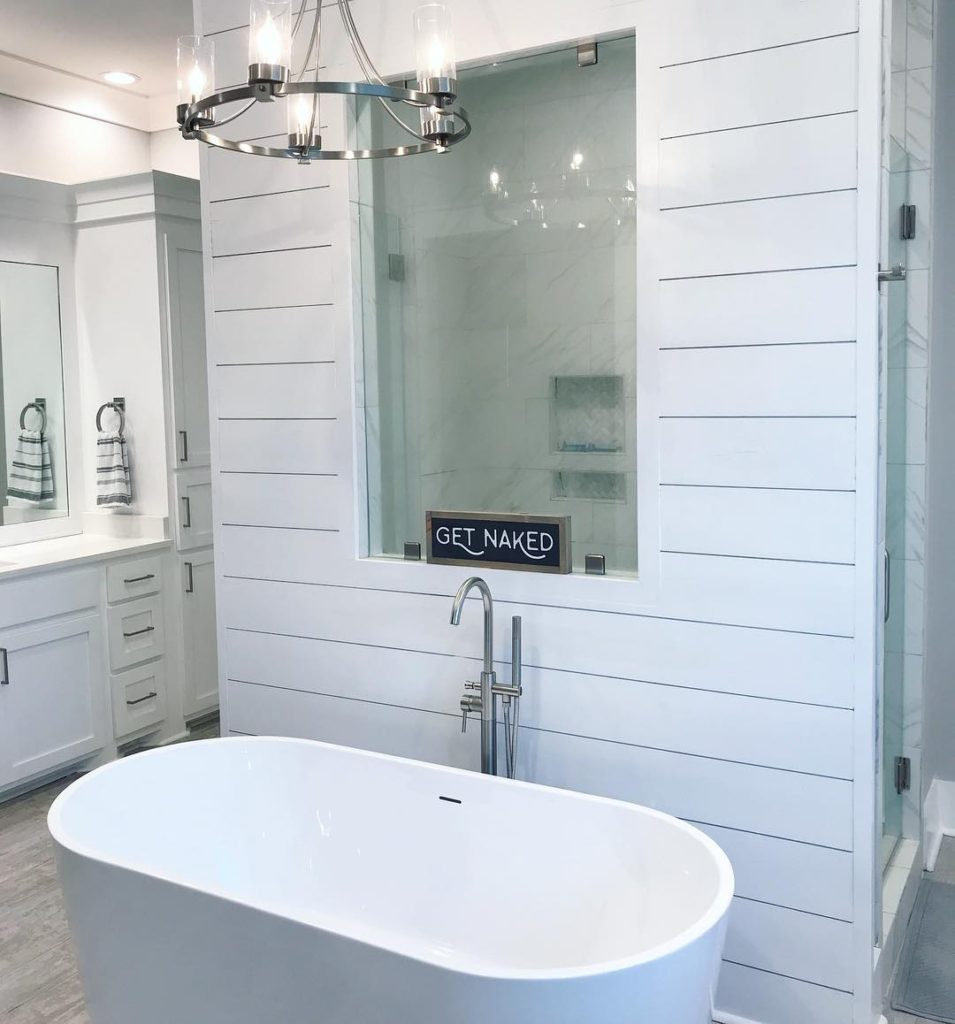 white bathroom with shiplap wall and bathroom cabinets