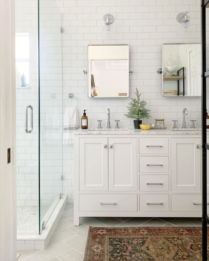 bathroom cabinet ideas for a white bathroom with white vanity and subway tile