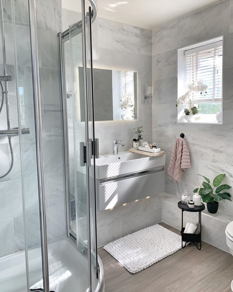 Bathroom with marble tile on walls with white rug