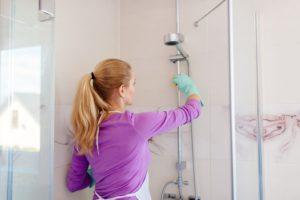 woman cleaning fiberglass shower