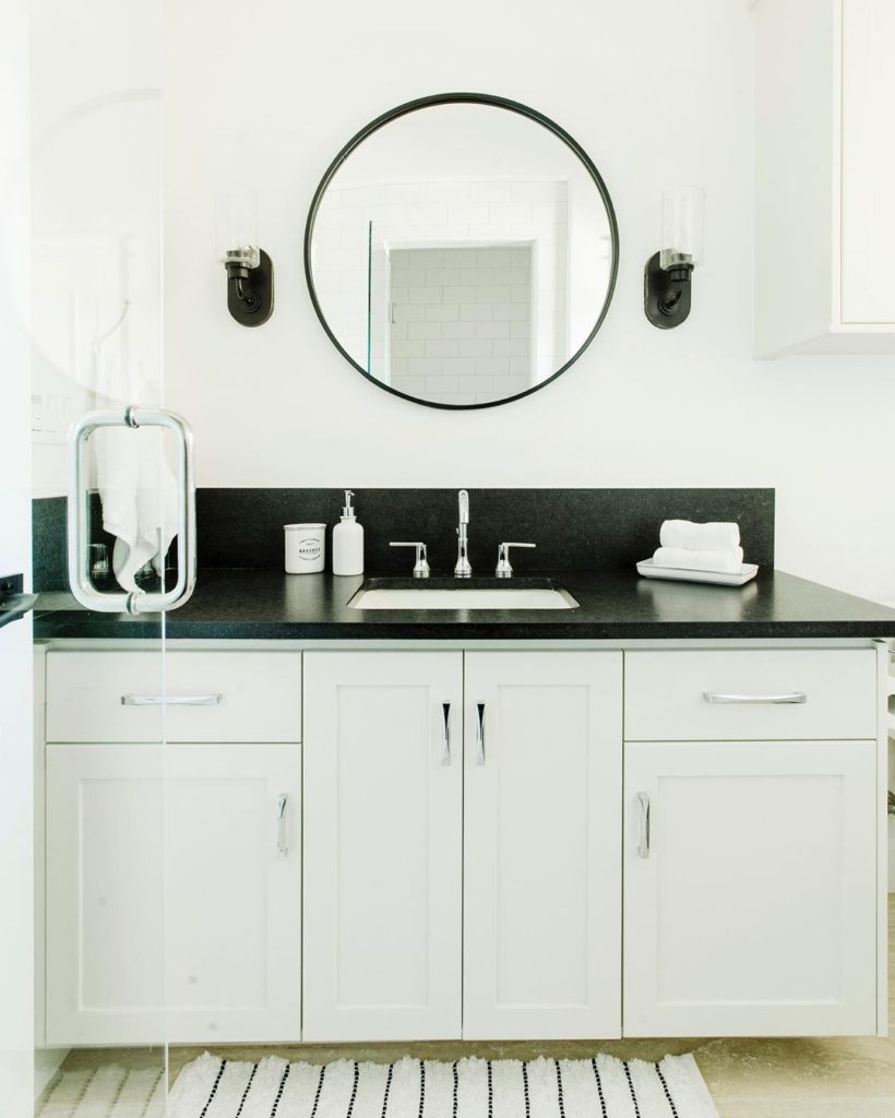 Black and white guest bathroom with black accents and black countertop