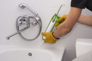 man caulking shower