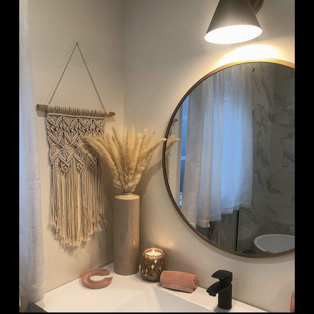 guest bathroom with macramé hanging and circular mirror