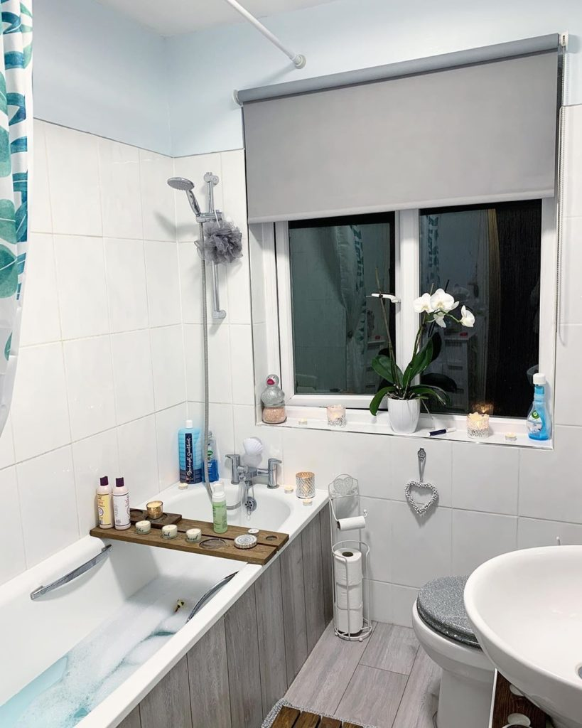 gray bathroom with bath tub and gray roller shade