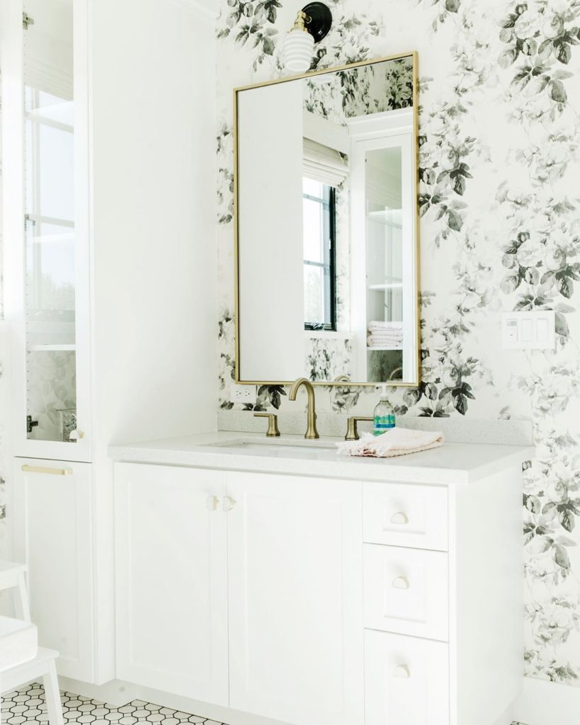 guest bathroom with floral wall paper and gold accented mirror