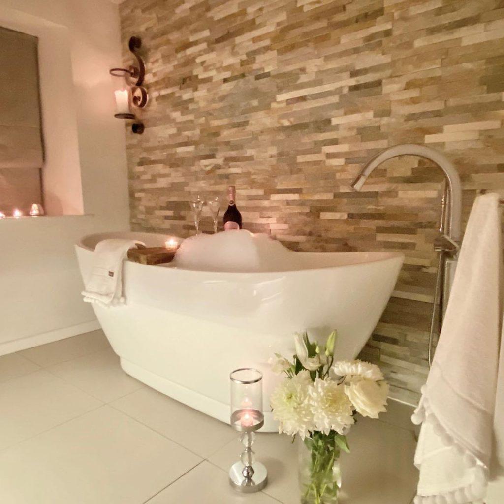 bath tub idea with stone back splash wall