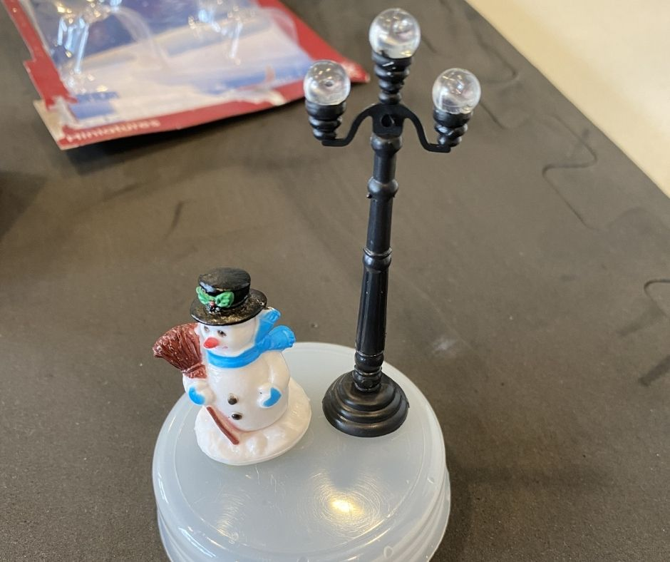 snow man figurine and lamp being glue down to snow globe base