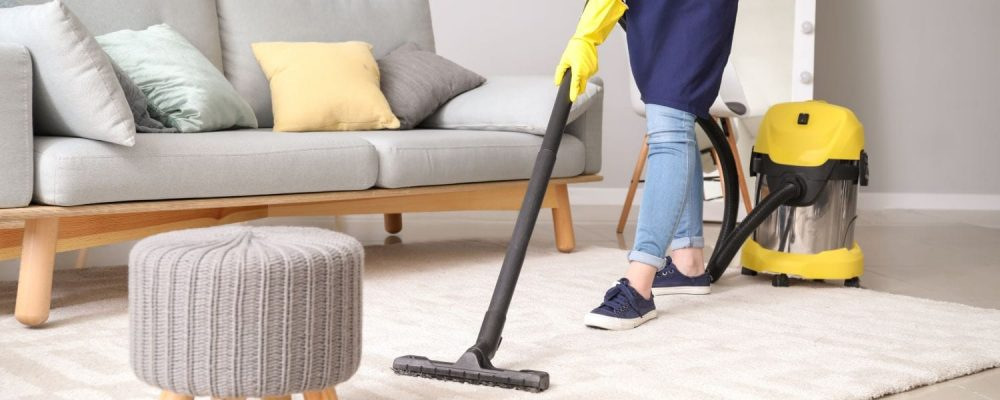 person cleaning an area rug
