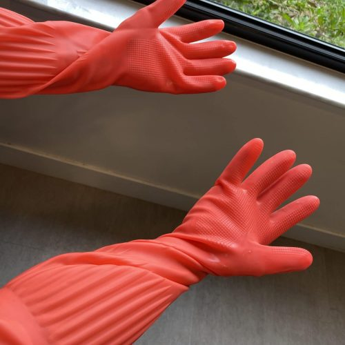 Bright red gloves on hands by a window