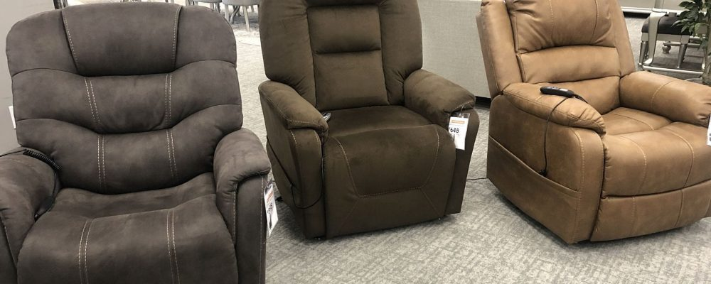 three recliners in a store with footrests